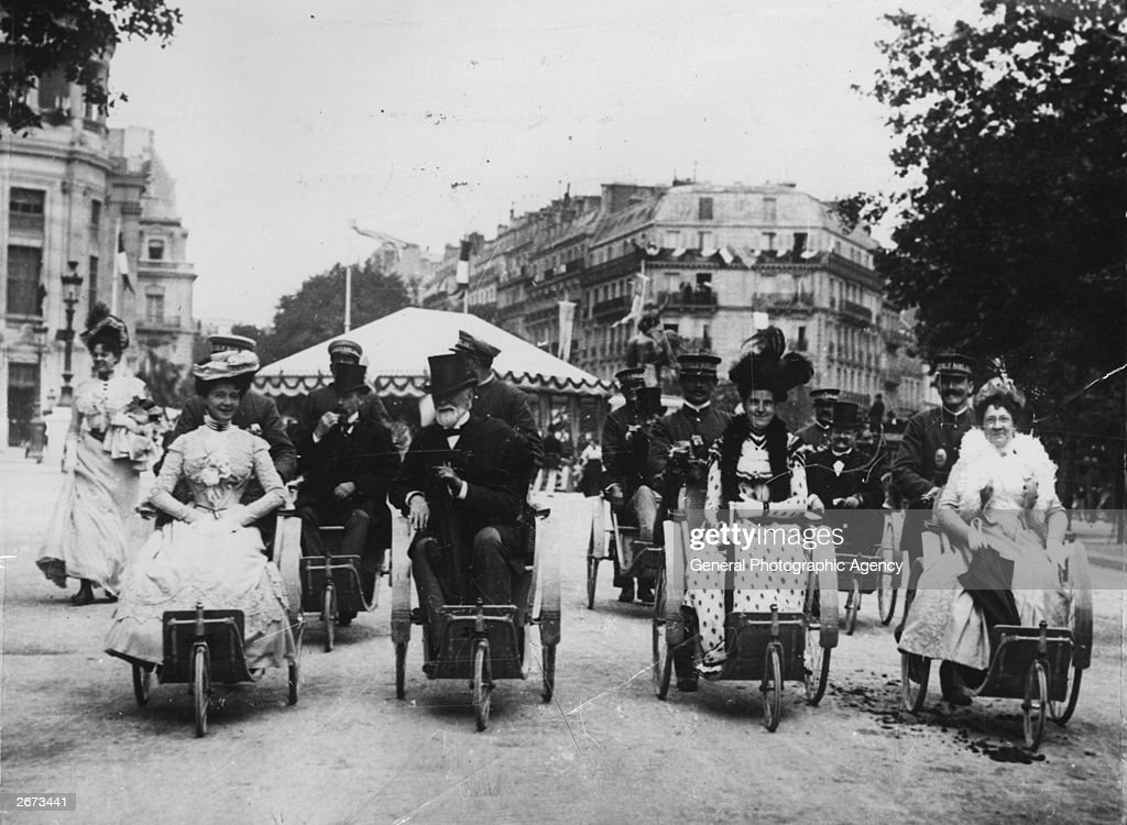 Visitors in Paris travelling to the International Exposition in bathchairs pushed by porters