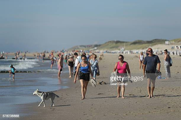 Visitors including a family with a dog who said they did not mind being photographed walk along a beach on Sylt Island on July 19 2016 near...