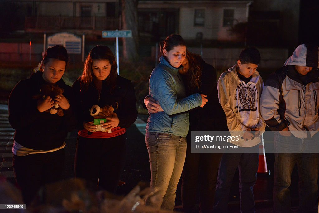 Visitors, including from left, Katelyn Jennings and Christine Jennings, both of Stratford, CT, and Greta Waag and Rachel Berger, both of Sherman, CT, visit a makeshift memorial in Sandy Hook on Tuesday, December 18, 2012, in Newtown, CT. Police say Adam Lanza, 20, fatally shot his mother, then drove to Sandy Hook Elementary in Newtown and killed 20 children, six adults and himself.