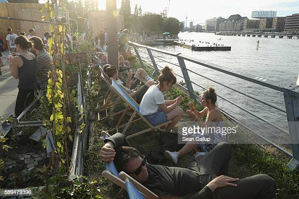 Visitors including people in the foreground who said they did not being photographed relax in lawn chairs along the Spree River on a warm summer...
