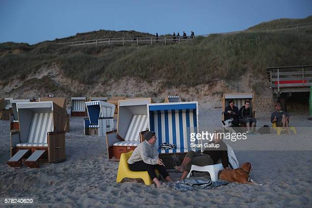 Visitors including two women with a dog who said they did not mind being photographed relax among beach chairs next to dunes at a beach after sunset...