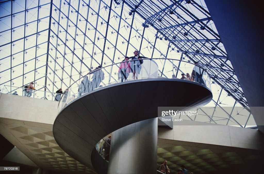 Visitors inside I. M. Pei's glass pyramid at the Louvre art museum in Paris, circa 1999.