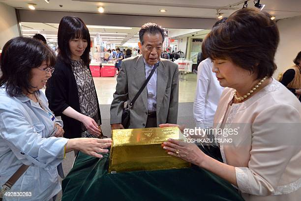 Visitors inspect a 120kg gold ingot displayed at the opening of the Gold Expo event at the Takashimaya department store in Yokohama suburban Tokyo on...