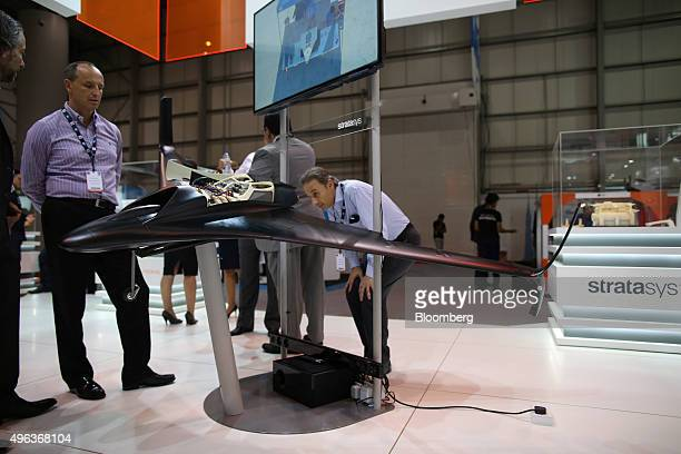 Visitors inspect a 3D printed drone at the Stratasys Ltd exhibition stand on the opening day of the 14th Dubai Air Show at Dubai World Central in...
