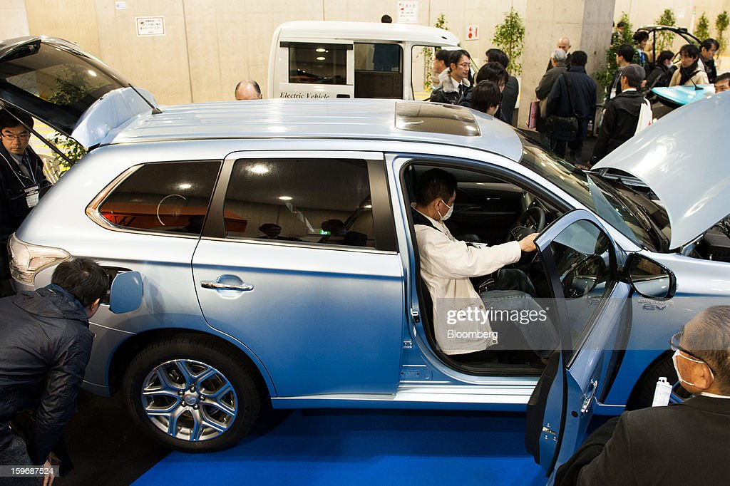 Visitors inspect a Mitsubishi Motors Corp. Outlander PHEV vehicle at Automotive World 2013 in Tokyo, Japan, on Friday, Jan. 18, 2013. The Automotive World 2013 trade show ends today. Photographer: Noriko Hayashi/Bloomberg via Getty Images
