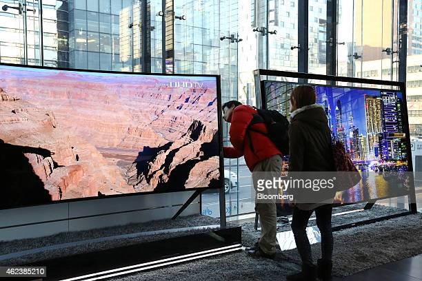 Visitors inspect a Samsung Electronics Co curved ultra high definition television at the company's d'light showroom in Seoul South Korea on Tuesday...