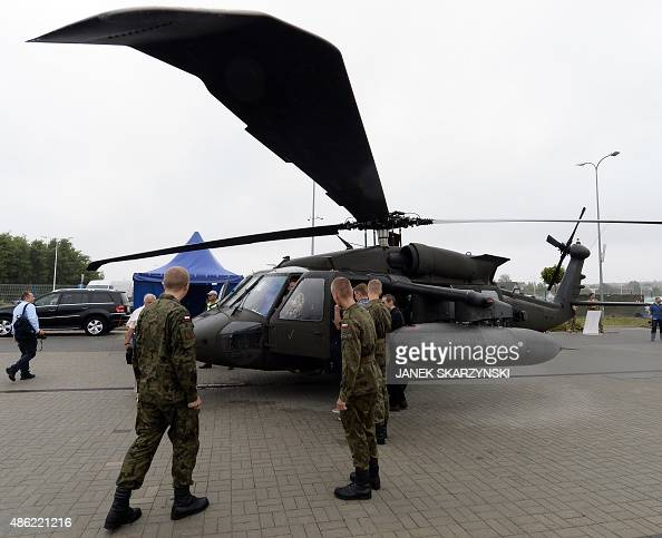 Visitors inspect a Sikorsky UH60 Black Hawk military helicopter during the 23rd International Defence Industry Exhibition MSPO in Kielce Poland on...