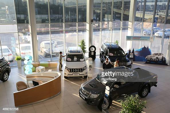 Visitors inspect a Toyota Hilux wagon right on display in the showroom of a Toyota Motor Corp automobile dealership in Moscow Russia on Wednesday Nov...