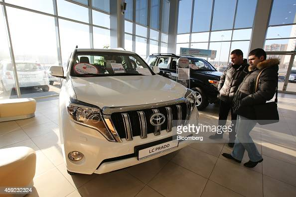 Visitors inspect a Toyota Land Cruiser Prado wagon on display in the showroom of a Toyota Motor Corp automobile dealership in Moscow Russia on...
