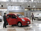 Visitors inspect a Toyota Passo at the company's showroom next to the headquarters in Toyota city Aichi prefecture on March 30 2010 Beleaguered...