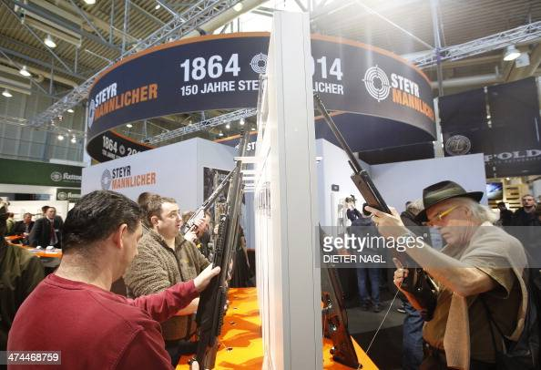 Visitors inspect hunting and sniper rifles at the 'Hohe Jagd' hunting fair on February 23 2014 in Salzburg Austria AFP PHOTO / DIETER NAGL