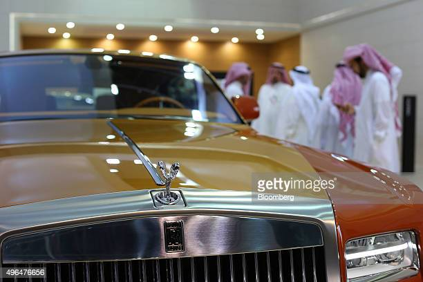 Visitors inspect luxury automobiles including a RollsRoyce Phantom Coupe luxury automobile center manufactured by RollsRoyce Motor Cars Ltd on...