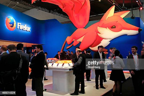 Visitors inspect mobile devices running Firefox OS operating system software at the company's pavilion at the Mobile World Congress in Barcelona...