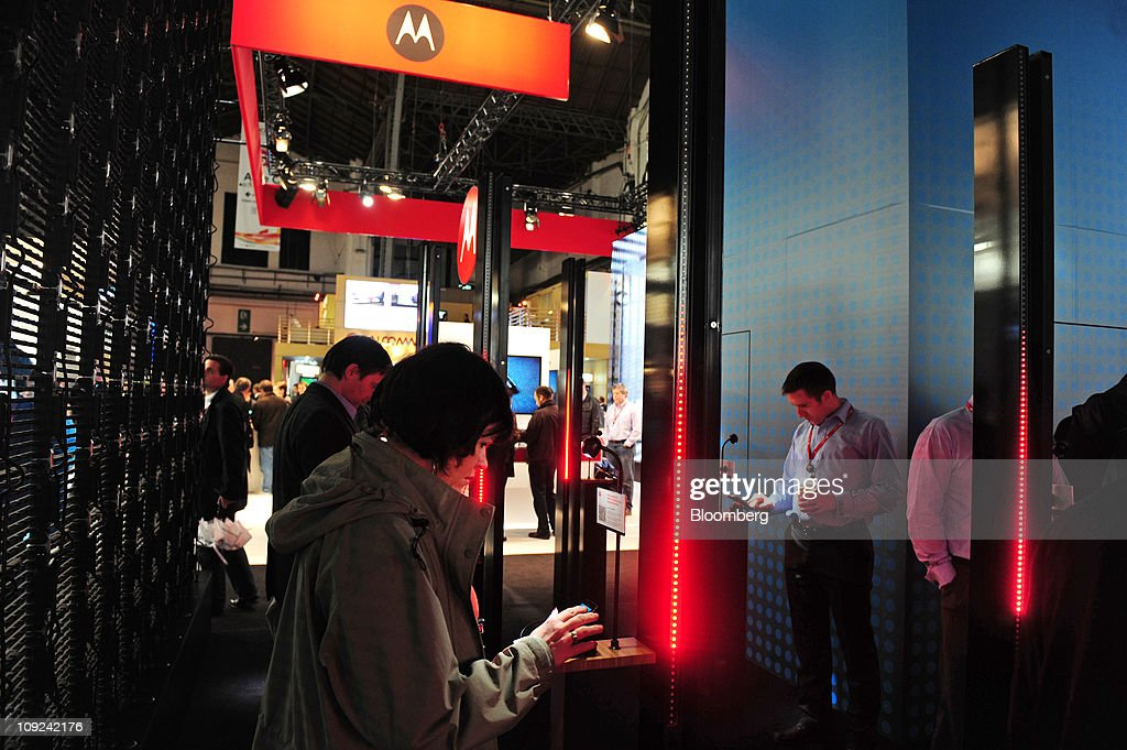 Visitors inspect Motorola Mobility Holdings Inc. mobile devices at the Mobile World Congress in Barcelona, Spain, on Thursday, Feb. 17, 2011. What makes the Atrix plausible as a netback replacement is the growing power being packed into smartphones. Photographer: Denis Doyle/Bloomberg via Getty Images