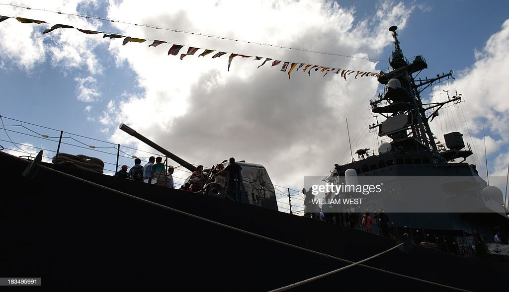 Visitors inspect the gun on the bow of the Japanese warship JS Makinami at Royal Australian Navy's Sydney base of Garden Island, during an open day after the Australian Navy celebrated 100 years since their first ships entered Sydney Harbour, on October 7, 2013. The open day followed the Royal Australian Navy International Fleet Review which also included visiting warships from Britain, Singapore, Japan, India, Thailand and the United States. AFP PHOTO/William WEST