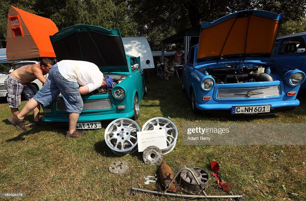 Visitors inspect Trabant automobiles as hubcaps are seen for sale at a Trabant enthusiasts' weekend on August 8 2015 near Nossen Germany The Trabant...