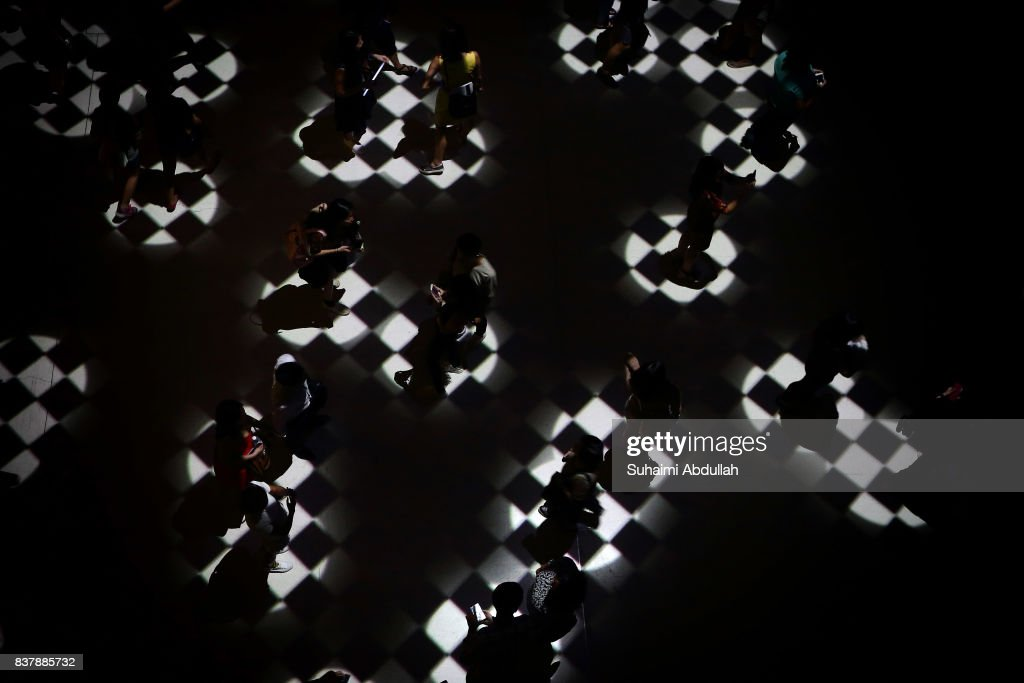 Visitors interact with light projections entitled 'Flock' by UK artists Tom Wexler and Kit Monkman during the Singapore Night Festival media preview on August 23, 2017 in Singapore.
