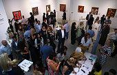 Visitors interacts during the VIP opening of the Dollarsandart 2015 Dubai Dollar Project 'Heroe$ Villain$' at RIRA Gallery on April 15 2015 in Dubai...