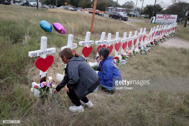 Visitors leave flowers at a memorial where 26 crosses were placed to honor the 26 victims killed at the First Baptist Church of Sutherland Springs on...