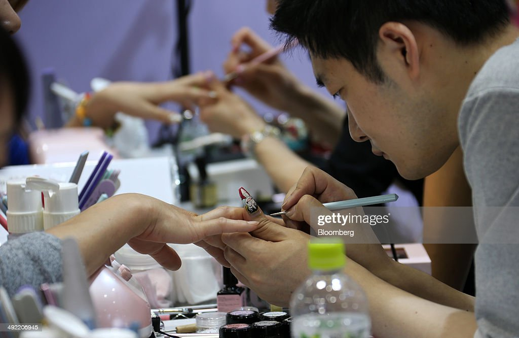 Visitors, left, get hand painted nail art on their nails at the Tokyo Nail Forum in Tokyo, Japan, on Monday, May 19, 2014. The trade fair hosted by Japan Nailist Association is held through May 21. Photographer: Tomohiro Ohsumi/Bloomberg via Getty Images