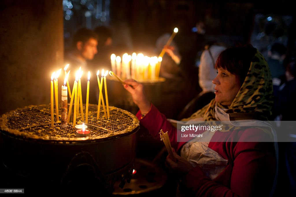 Visitors light candles in the Church of the Nativity on December 24 2014 in Bethlehem West Bank Every Christmas pilgrims travel to the church where a...