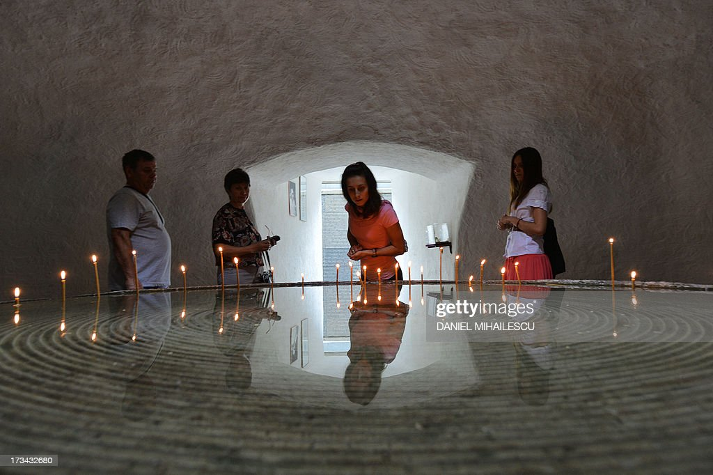 Visitors light up candles inside a room 'The space for Recollection and Prayer' to commemorate victims of the communist repression in Romania, in Sighetu Marmatiei on July 13, 2013. Former dissidents and political prisoners gathered in Romania on July 14, 2013 at a museum commemorating those who suffered abuses under communism, set up 20 years ago at the site of a prison where scores died. AFP PHOTO / DANIEL MIHAILESCU