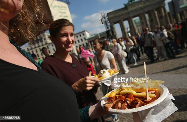 Visitors line up to buy currywurst and french fries on German Unity Day near the Brandenburg Gate on October 3 2014 in Berlin Germany Germany is...
