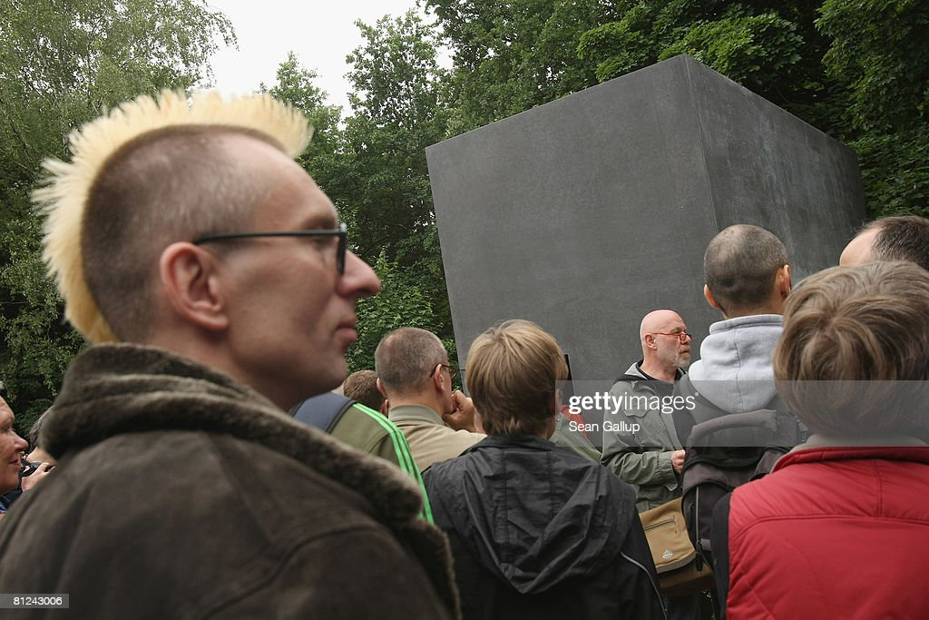 Visitors line up to peek into the window of the just-inaugurated memorial to homosexual victims of the Nazis on May 27, 2008 in Berlin, Germany. The memorial, a large stone with a window that looks onto an image of two men kissing, commemorates the tens of thousands of gays imprisoned by the Nazis, including the estimated 15,000 sent to concentration camps. The memorial stands in the Tiergarten park close the to Holocaust Memorial.
