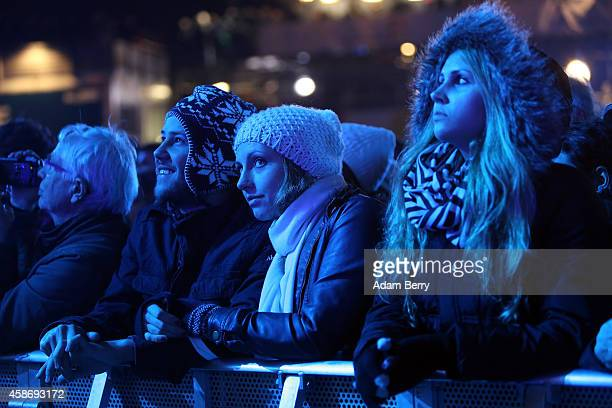 Visitors listen during celebrations for the 25th anniversary of the fall of the Berlin Wall at the Brandenburg Gate on November 9 2014 in Berlin...