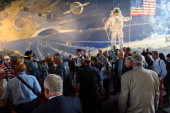 Visitors listen to a tourist guide at the Smithsonian's National Air and Space Museum after the museum's reopening following a bipartisan bill passed...