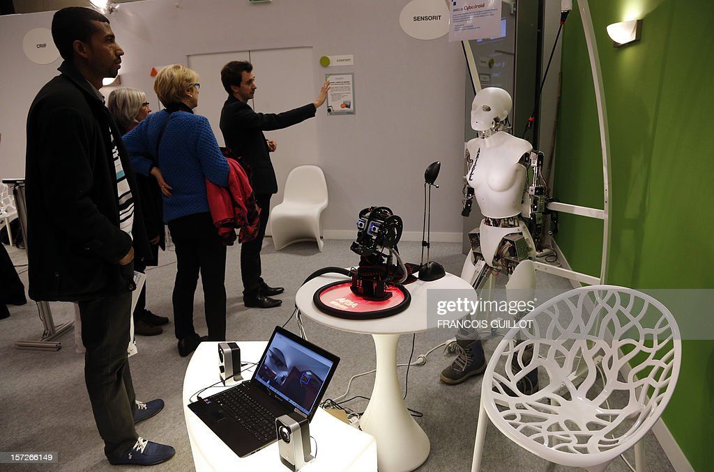 Visitors listen to explanations from an exhibitor at a stand where a humanoid robot called ARIELL (R) designed by French robotic start-up company Cybedroid, is displayed on December 1, 2012 during a fair dedicated to services to the elderly and the disabled, at the Porte de Versailles congress hall in Paris. AFP PHOTO FRANCOIS GUILLOT