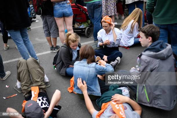 Visitors listen to the speech of former President of the United States of America Barack Obama and German chancellor Angela Merkel at Brandenburg...
