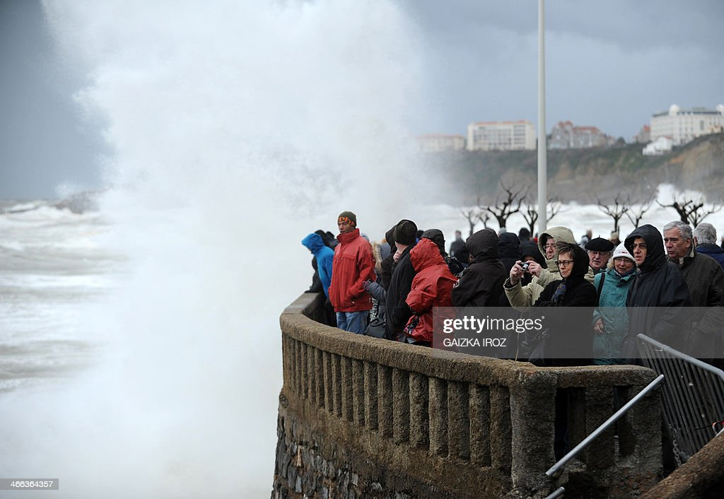 Visitors llok at strong waves from the Atlantic Ocean in Biarritz, southwesten France, during high tides in February 1, 2014. French departments on the Atlantic coast were on alert for strong waves and risk of submersion on January 31, and the western department of Finistere was on high alert for flooding.