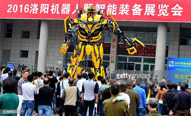 Visitors look a 'Bumblebee' transformer robot on first opening day of the China Luoyang International Robot and Intelligent Equipment Exhibition on...