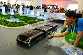 Visitors look a scale model of a Transit Elevated Bus during the ongoing 19th China Beijing International Hightech Expo on May 20 2016 in Beijing...