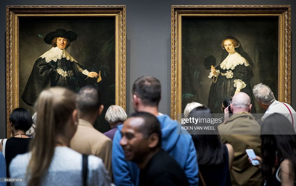 Visitors look and take pictures of Marten and Oopjen, two Rembrandt portraits of a wedding couple jointly bought by the Netherlands and France, and that are displayed at the Rijksmuseum in Amsterdam, on July 01 2016. / AFP / ANP / Koen van Weel / Netherlands OUT