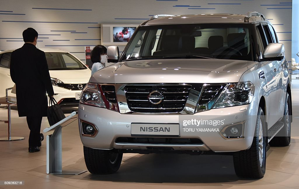 Visitors look around vehicles at the showroom of the headquarters of Japan's auto maker Nissan Motor in Yokohama, suburb of Tokyo, on February 10, 2016. AFP PHOTO / Toru YAMANAKA / AFP / TORU YAMANAKA