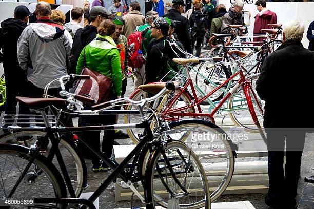 Visitors look at a bicycle on display at the Berliner Fahrradschau bicycle trade fair on March 22 2014 in Berlin Germany The fair which features the...