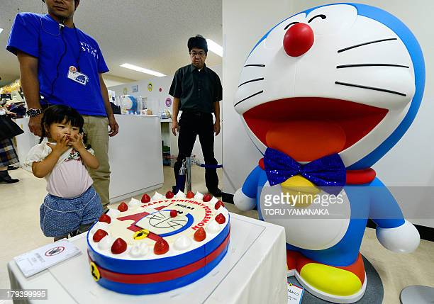 Visitors look at a birthday cake displayed next to a large figure of Japanese anime manga character Doraemon to celebrate his birthday during the...