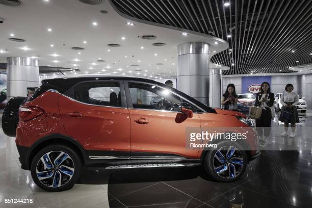 Visitors look at a BYD vehicle on display at the company's headquarters in Shenzhen China on Thursday Sept 21 2017 China will likely order an end to...