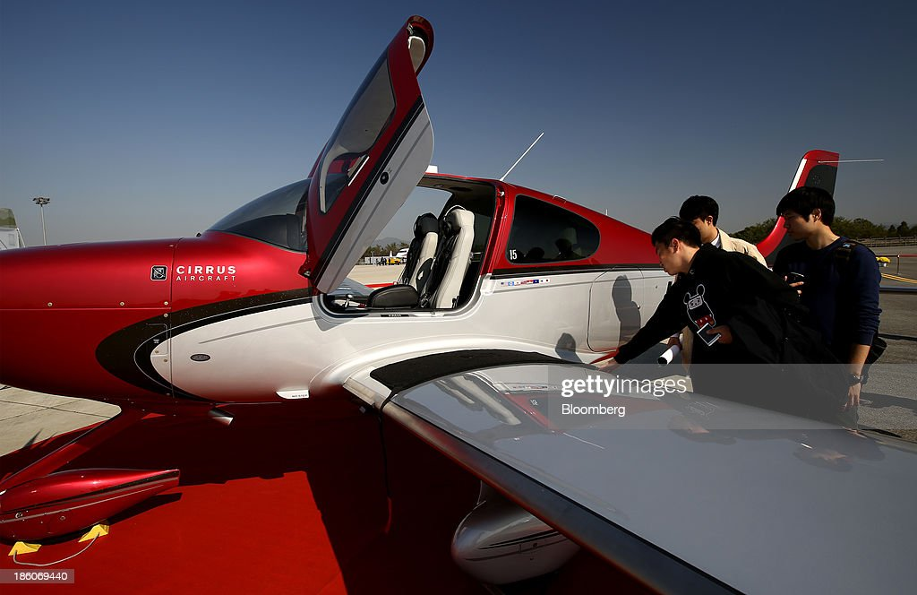 Visitors look at a Cirrus SR-22 aircraft during the Cheongju International Airport Air Show on the sidelines of the Seoul International Aerospace & Defense Exhibition 2013 at Cheongju International Airport in Cheongju, South Korea, on Friday, Oct. 25, 2013. The exhibition will run till Nov. 3. Photographer: SeongJoon Cho/Bloomberg via Getty Images