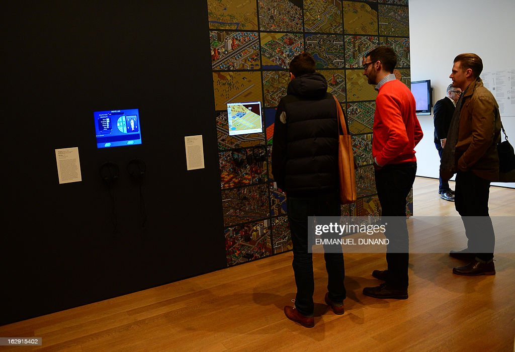 Visitors look at a demonstration of the video game SimCity (2000) during an exhibition preview featuring 14 video games acquired by The Museum of Modern Art (MoMA) in New York, March 1, 2013. The MoMA acquired 14 video games entering its collection as part of an ongoing research on interaction design.