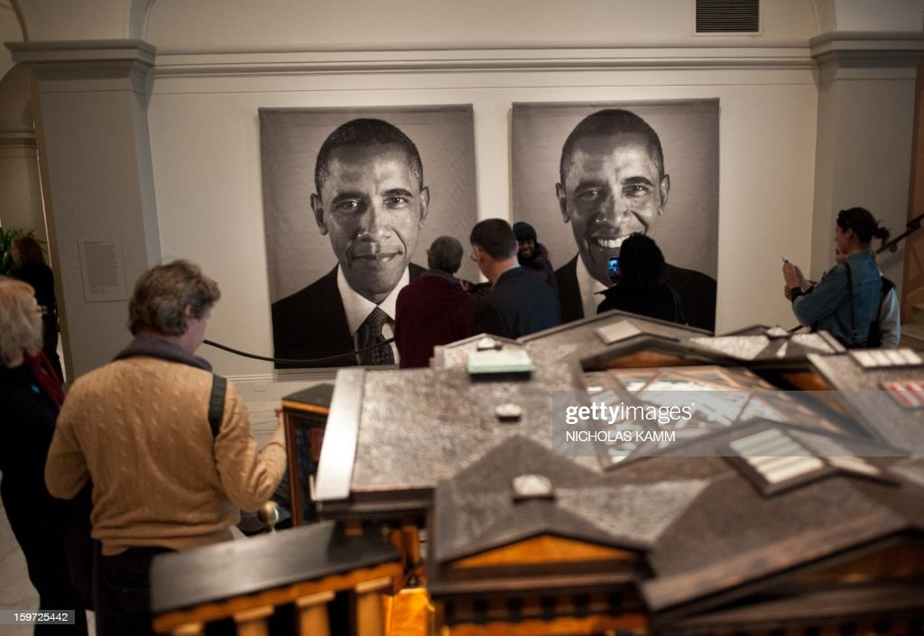 Visitors look at a diptych of US President Barack Obama by Chuck Close at the National Portrait Gallery in Washington on January 19, 2013, two days before Obama's second inauguration. AFP PHOTO/Nicholas KAMM = MANDATORY MENTION OF THE ARTIST UPON PUBLICATION =