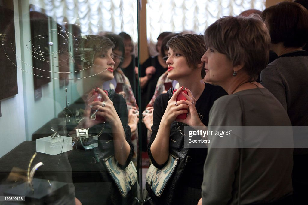 Visitors look at a display of luxury diamond art jewelry exhibited at the Kremlin Museum by OAO Alrosa in Moscow, Russia, on Thursday, April 11, 2013. OAO Alrosa may be valued at $9.4-10.8B when the Russian government looks to sell stake in the company in November, Vedomosti newspaper says, citing two unidentified bankers close to Goldman Sachs. Photographer: Alexander Zemlianichenko Jr./Bloomberg via Getty Images
