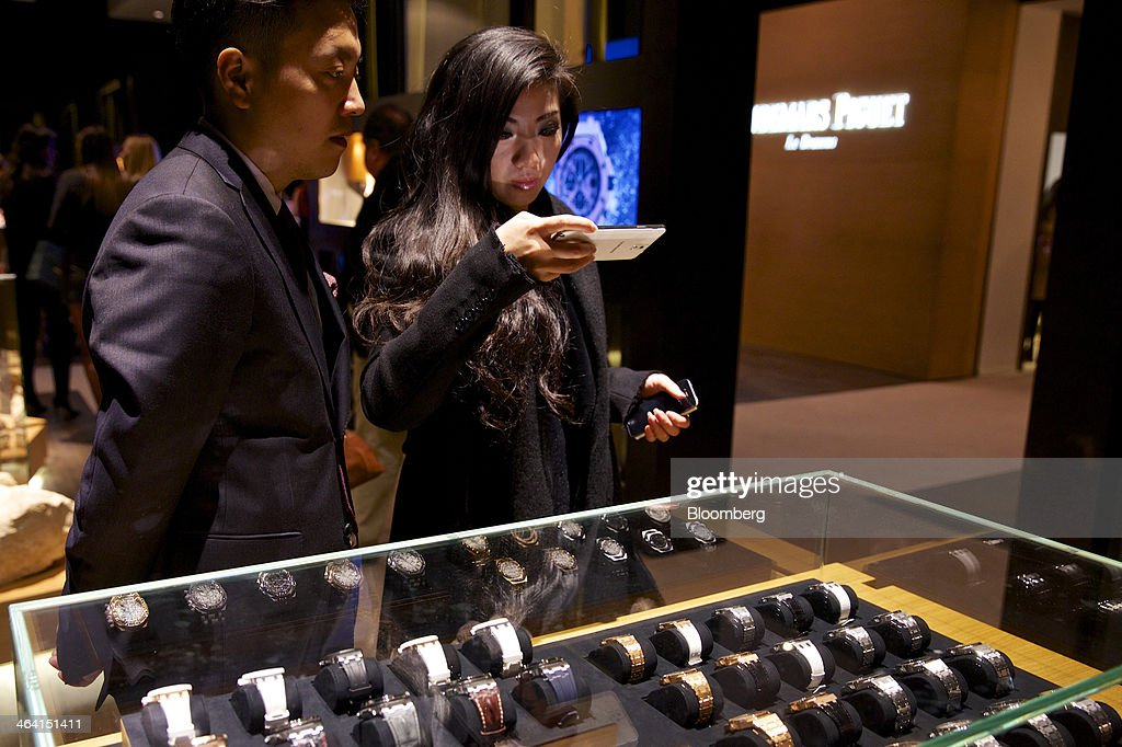 Visitors look at a display of luxury wristwatches manufactured by Audemars Piguet at the Salon International de la Haute Horlogerie (SIHH) watch fair in Geneva, Switzerland, on Monday, Jan. 20, 2014. Enthusiasts coveting $50,000 Cartier watches at the Swiss industry's annual fair bumped opening meetings to resolve the three-year-old Syrian civil war out of the lakeside town. Photographer: Gianluca Colla/Bloomberg via Getty Images