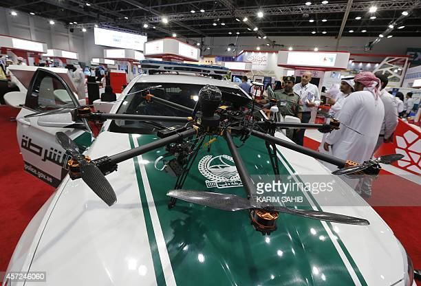 Visitors look at a drone equipped with cameras on a police car at the Gitex Technology week in Dubai on October 15 2014 Dubai police are introducing...