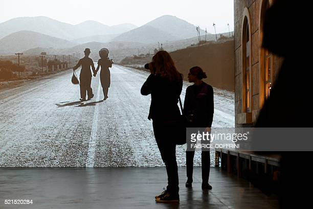 Visitors look at a film projection during a press visit of Chaplin's World Museum in CorsiersurVevey western Switzerland on April 16 2016 Imagine...