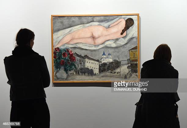 Visitors look at a FrenchRussian artist Marc Chagall's painting during the 'Chagall Retrospective' exhibition at the Royal Museum of Fine Arts of...
