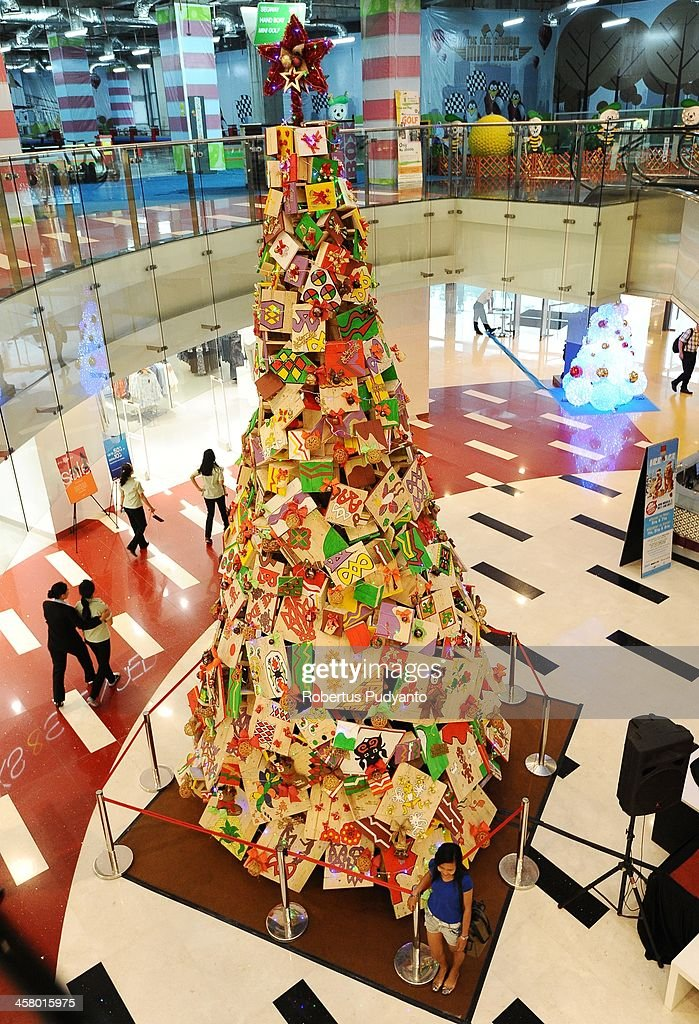 Visitors look at a giant Christmas tree made of 100 wooden benches and 60 wooden tables height 7,5 meters displays at Grand City Mall on December 19, 2013 in Surabaya, Indonesia. Indonesian Christians celebrate holiday season while on December 12, Indonesian police warned that Islamic extremists may be planning to target worshipers at Christmas and New Years celebrations in the capital Jakarta and other parts of the country.