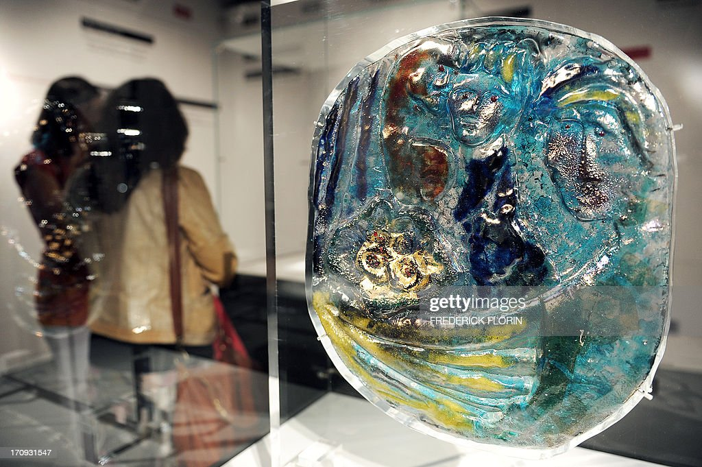 Visitors look at a glass sculpture entitled 'Fidanzatini' made in 1954 by Italian artist Egidio Costantini with the collaboration of Marc Chagall, on June 20, 2013 in the Lalique Museum in Wingen-sur-Moder, eastern France, before the opening day of the exhibition 'Le verre et les grands maitres de l'art moderne' (Glass and masters of modern art). The event will run from June 21 till November 3, 2013.